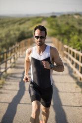 Athlete running in rural landscape - JASF000771