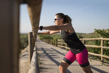 Sportive woman stretching on a bridge - JASF000774