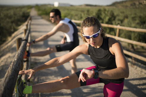 Sportive woman with smartwatch and man stretching on a bridge - JASF000777