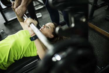 Woman training bench press at gym with assistance - JASF000782