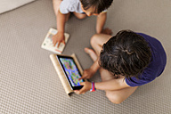 Litte boy sitting on the floor using digital tablet while his brother is watching - VABF000527
