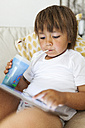 Litte boy sitting on couch using digital tablet while drinking something - VABF000530