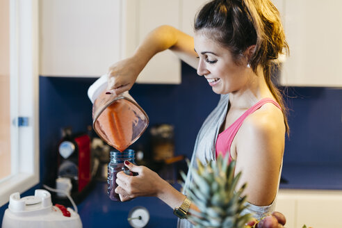 Smiling young woman in kitchen pouring smoothie into mug - JRFF000736