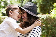 Happy mother and son hugging outdoors - VABF000532