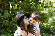 Mother kissing son outdoors - VABF000541