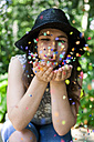 Young woman playing with confetti - VABF000550