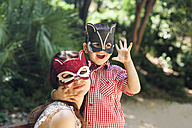 Mother and little son with animal masks playing in the park - VABF000565