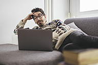 Suprised man lying on a couch looking at laptop - LCUF000019