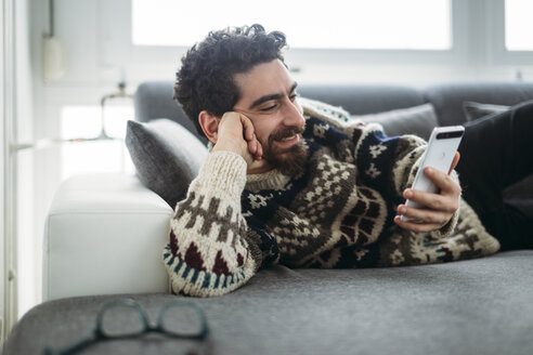 Smiling man lying on a couch looking at phablet - LCUF000022