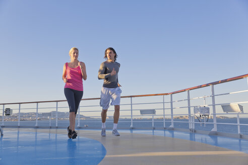 Young couple is jogging around the shipdeck of a cruise ship, Mediterranean Sea - ONBF000059