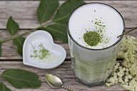 Matcha tea with milk in glass on wood, elderflowers and heart shaped porcellain bowl - YFF000548