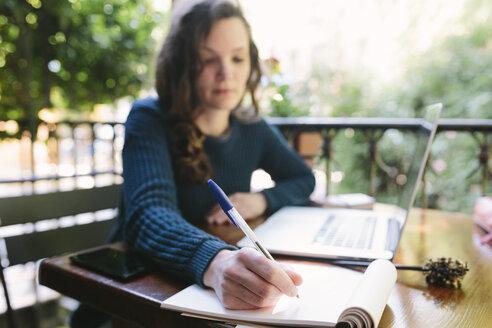 Young woman sitting on balcony using laptop - BOYF000371