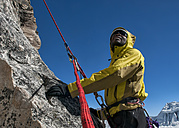 Nepal, Himalaya, Solo Khumbu, Everest region Ama Dablam, mountaineer with rope at rock face looking up - ALRF000510