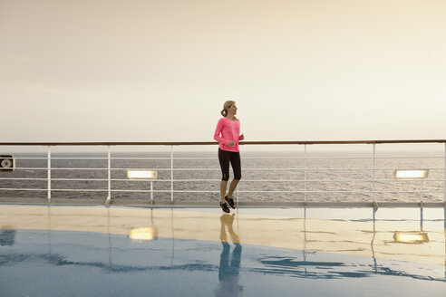 Young woman doing exercises on a shipdeck, cruise ship, Mediteranean Sea - ONBF000061