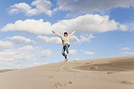 Enthusiastic mature woman jumping over sand dune - GWF004735