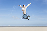 Enthusiastic mature woman jumping on beach - GWF004738