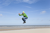 Enthusiastic mature man jumping on beach - GWF004741