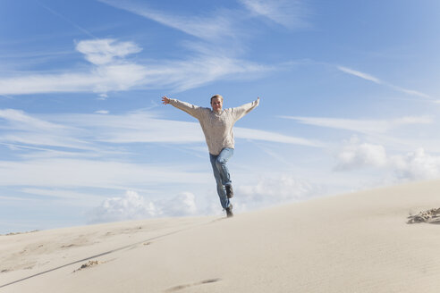 Enthusiastic mature woman running along sand dune - GWF004744