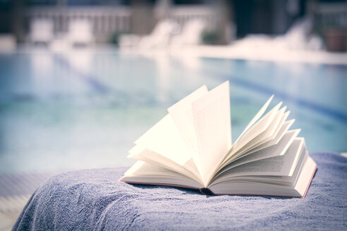 Opened book on towel at swimming pool - CMF000468