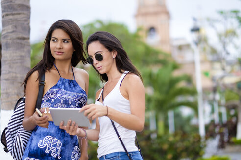Mexico, Puerto Vallarta, two young women with tablet - ABAF002037