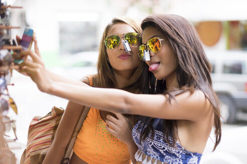 Two young women trying sunglasses on and taking a selfie - ABAF002046