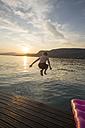Italy, Veneto, Bardolino, Lake Garda, boy jumping into the water at sunset - SARF002736