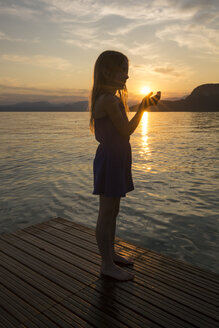 Girl holding hands against the sun at sunset - SARF002739