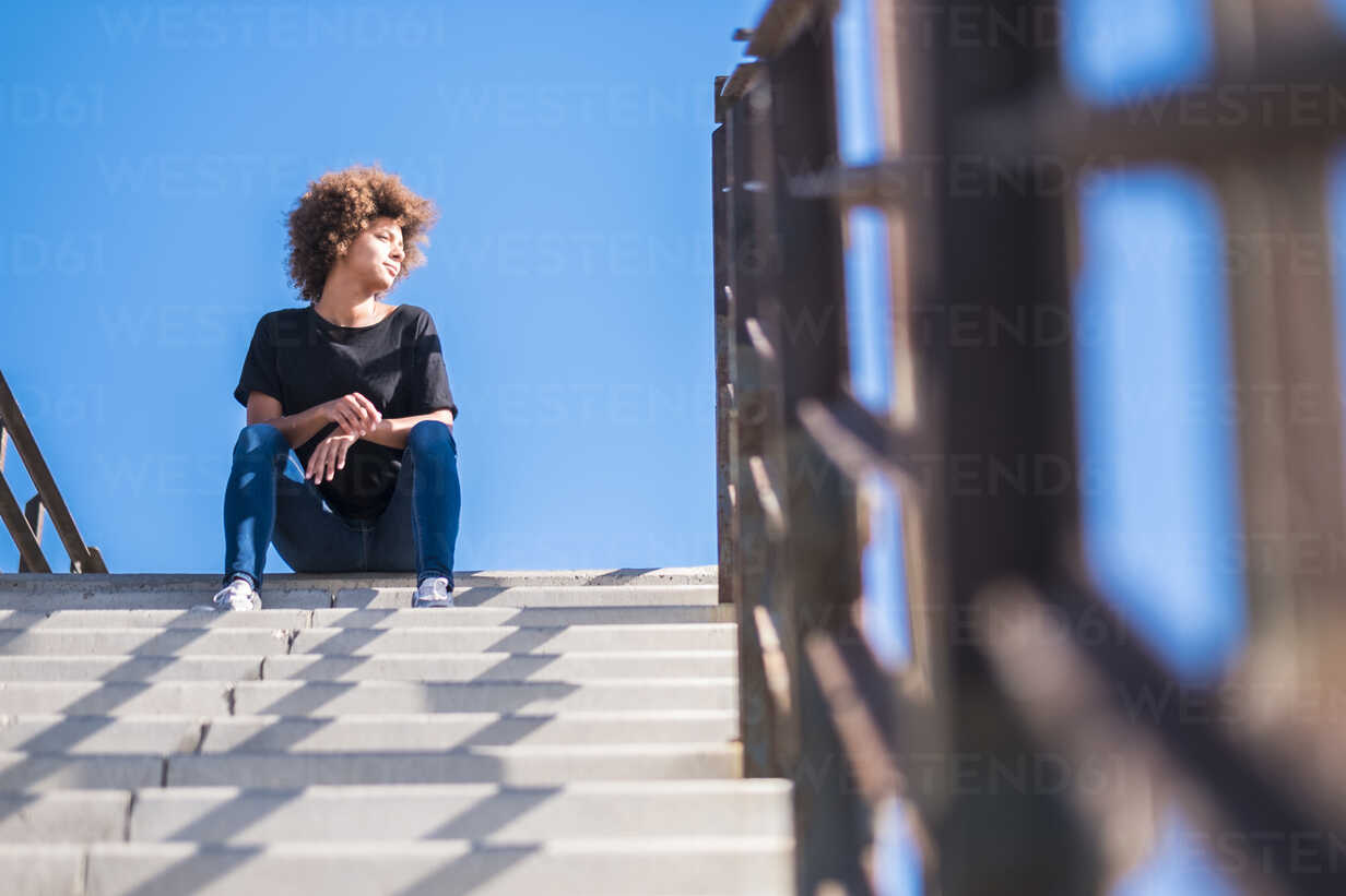 Woman sitting on stairs at sunlight - SIPF000527 - Simona Pilolla/Westend61