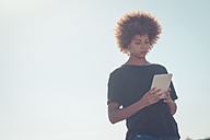 Woman at backlight looking at digital tablet - SIPF000530