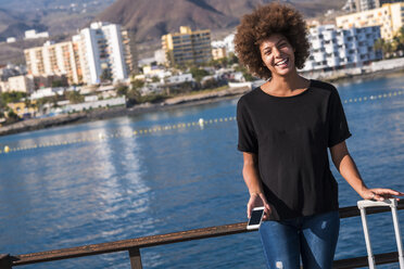Spain, Tenerife, portrait of laughing young woman standing on deck with smartphone and suitcase - SIPF000533
