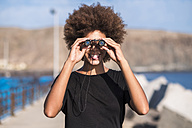 Smiling young woman with binocular - SIPF000536