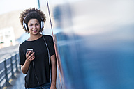 Portrait of smiling young woman with headphones and smartphone leaning against wall - SIPF000539