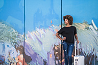 Spain, Tenerife, young woman with rolling suitcase waiting in front of painted wall - SIP000542