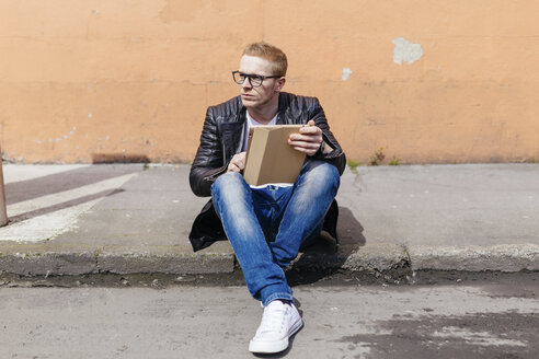 Young man with digital tablet sitting at curb - BOYF000410