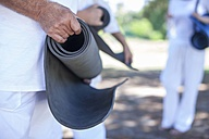 Elderly man rolling up fitness mat outdoors - ZEF008687