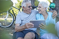 Happy elderly couple sitting outdoors with digital tablet - ZEF008708