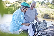 Elderly woman on bicycle and man talking - ZEF008711