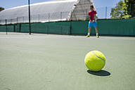 Tennis ball with unfocused tennis player in the background - ABZF000656