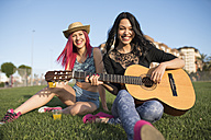 Friends sitting on grass playing guitar - JASF000815