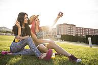 Friends sitting on grass taking selfies - JASF000827