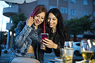 Two friends sitting in bar using smart phone - JASF000851