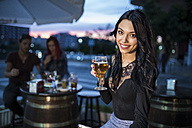 Young woman sitting in bar, drinking beer - JASF000854