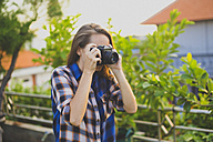 Woman using vintage camera - KNTF000329