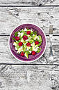 Bowl of avocado raspberry salad with feta on wood - LVF004942
