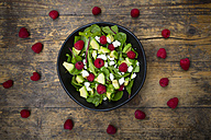 Bowl of avocado raspberry salad with feta on dark wood - LVF004945