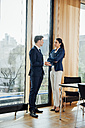 Businessman and businesswoman in office talking at the window - CHAF001770