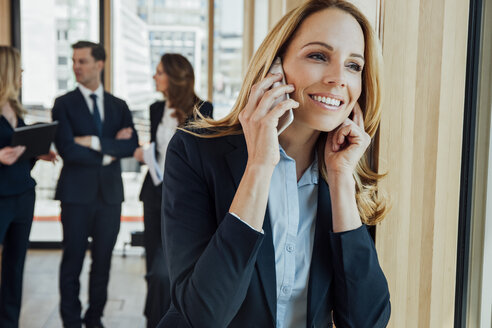 Smiling businesswoman in office on cell phone with businesspeople in background - CHAF001785