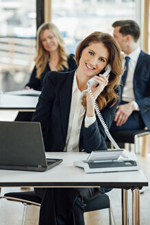 Smiling businesswoman at office desk on the phone - CHAF001788
