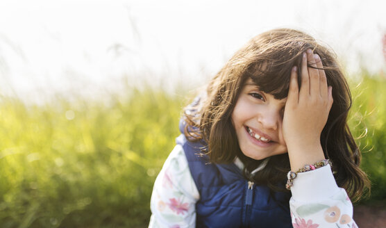 Portrait of smiling little girl covering eye with her hand - MGOF001933