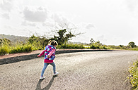Back view of little girl walking on country road - MGOF001936